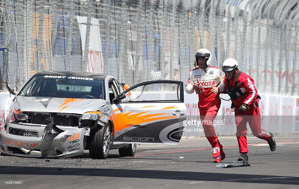 LONG BEACH, CA - APRIL 14: Actor Brody Jenner (L) runs off the track with a safety crew member after crashing his car during the 36th Annual Toyota Pro/Celebrity Race held at the Toyota Grand Prix of Long Beach on April 14, 2012 in Long Beach, California. (Photo by Ryan Miller/Getty Images)  *** Local Caption ***  Brody Jenner